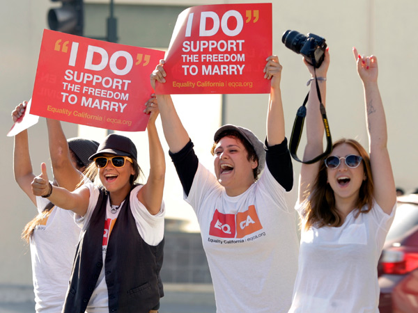 Gay-rights supporters, from left, Briana Castaneda, Aimee Mendez and Gal Bar-El celebrate on Santa Monica Boulevard after the U.S. Supreme Court rulings in West Hollywood, Calif., Wednesday, June 26, 2013. (AP Photo/Jason Redmond)