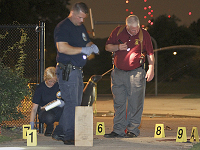 Homicide investigators look at the crime scene at Mander playground in the Strawberry Mansion section of Philadelphia early Monday, where four people were shot and one was killed. (For the Inquirer and Daily News / Joseph Kaczmarek)