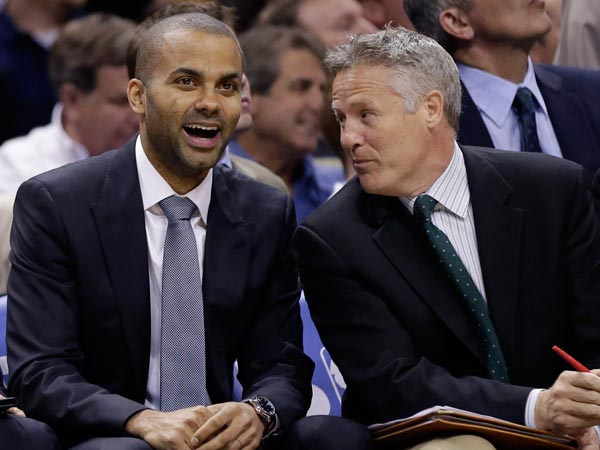 Tony Parker, left, of France, sits with assistant coach Brett Brown during the second half of an NBA basketball game, Wednesday, March 6, 2013, in San Antonio. Parked is out with a sprained ankle. (Eric Gay/AP file)