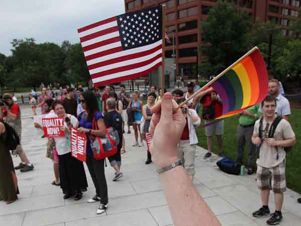 Janice Rael waves two flags during a rally in support of Wednesday´s landmark SCOTUS gay-marriage ruling, on the Independence Mall,  Wednesday, June 26, 2013.  (  Steven M. Falk / Staff Photographer )