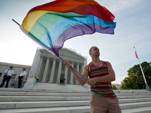 Gay rights advocate Vin Testa waves a rainbow flag in front of the Supreme Court at sun up in Washington, Wednesday, June 26, 2013. (AP Photo/J. Scott Applewhite)