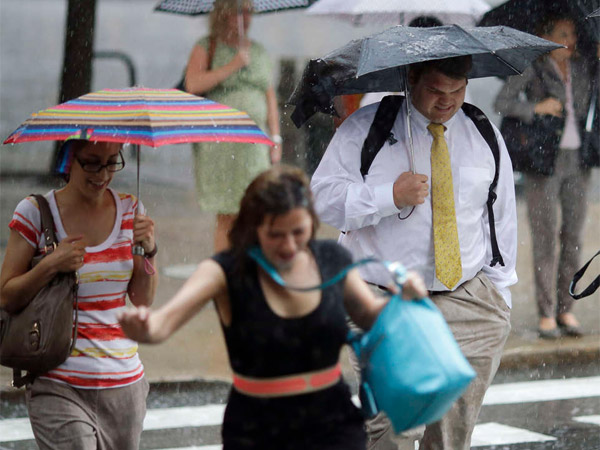 Pedestrians scramble as a fast-moving rainstorm rolls through Philadelphia.