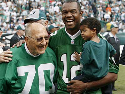 Randall Cunningham holds his son, Christian, during halftime of an Eagles game last season. Former Eagle Al Wistert on the left. ( David Maialetti / Staff Photographer)