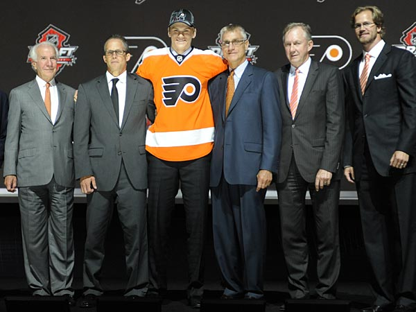 Defenseman Samuel Morin stands with officials from the Philadelphia Flyers after being chosen 11th overall in the first round of the NHL draft. (Bill Kostroun/AP)