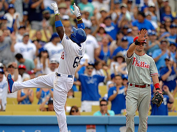 The Dodgers´ Yasiel Puig points to the sky after hitting a triple as Phillies third baseman Michael Young looks on during the fifth inning. (Mark J. Terrill/AP)