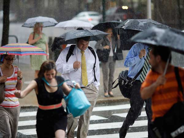 Pedestrians scramble through a rain storm during an evening commute in Philadelphia in June. (AP Photo/Matt Slocum)