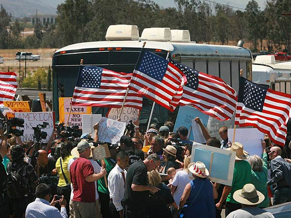 Protesters turn back three buses carrying 140 immigrants as they attempt to enter the Murrieta U.S. Border Patrol station for processing on Tuesday, July 1, 2014, in Murrieta, Calif. (AP Photo/The Press-Enterprise, David Bauman)  MANDATORY CREDIT