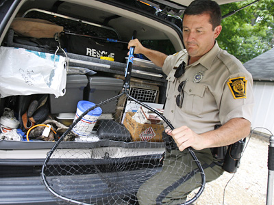 The long arm of the law, in his case, wields an animal snare. Jerrold Czech Jr., Philadelphia's only wildlife conservation officer, prepares to take another critter into protective custody. (Elizabeth Robertson / Staff Photographer)<br />
