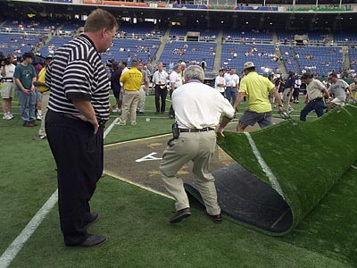 Andy Reid watches members of the grounds crew at Veterans Stadium work with the artificial turf. (Ron Cortes / Staff file photo)