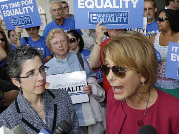 State Sen. Barbara Buono speaks to  advocates for gay marriage in New Jersey at a gathering outside the Statehouse Thursday, June 27, 2013, in Trenton, N.J., as they say they´ll press their case in the Legislature and the courts after the U.S. Supreme Court ruling that invalidates parts of the federal Defense of Marriage Act. Gov. Chris Christie said he would again veto a same-sex marriage bill if it reaches his desk, and that Wednesday´s U.S. Supreme Court ruling striking down a ban on federal benefits for same-sex married couples will have no effect on New Jersey, one of a handful of states that allows civil unions. Buono, the Democrat running against Christie for governor and the parent of an adult gay daughter, called for an override of Christie´s veto. (AP Photo/Mel Evans)