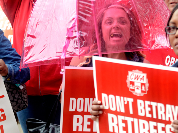 Carly Almodovar, (under umbrella) a staff representative at the CWA union´s Local 1034 Southern District in Woodbury Heights, joins other members at a Statehouse rally in Trenton, June 12, 2013, marching from the War Memorial to protest Gov. Christie´s plan to reduce payments to their pension fund to fill a $1.7 billion revenue gap. A state judge will consider whether Christie´s plan is legal. (TOM GRALISH/Staff Photographer)