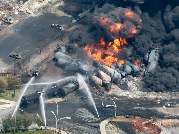Smoke rises from railway cars that were carrying crude oil after derailing in downtown Lac Megantic, Quebec, Canada, Saturday, July 6, 2013. A large swath of Lac Megantic was destroyed Saturday after a train carrying crude oil derailed, sparking several explosions and forcing the evacuation of up to 1,000 people.