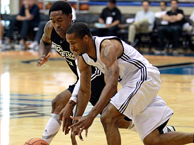 The Nets´ MarShon Brooks, left, and the 76ers´ Clay Tucker scramble after a loose ball. (John Raoux/AP)