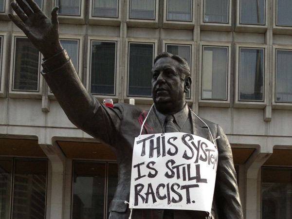 A statue of former Philadelphia Mayor Frank Rizzo in front of the Municipal Services Building on John F. Kennedy Boulevard across from City Hall was decorated with signs protesting the acquittal of George Zimmerman in the fatal shooting of Trayvon Martin.