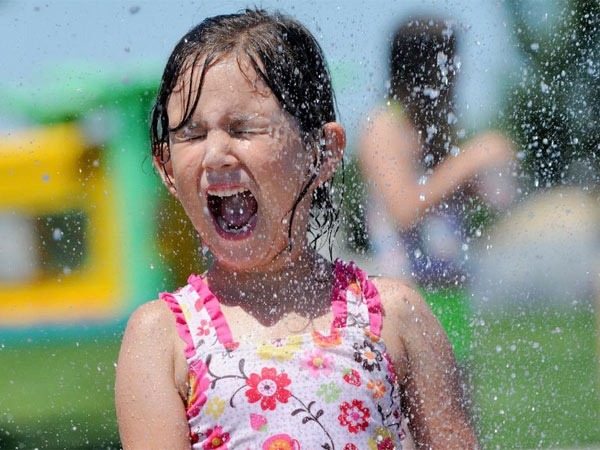 Kayla Holdridge is sprayed with water in an attempt to beat the heat. Philly is about to experience another six or seven day heat wave, marked by high humidity. (AP Photo/The Idaho Press-Tribune, Adam Eschbach)