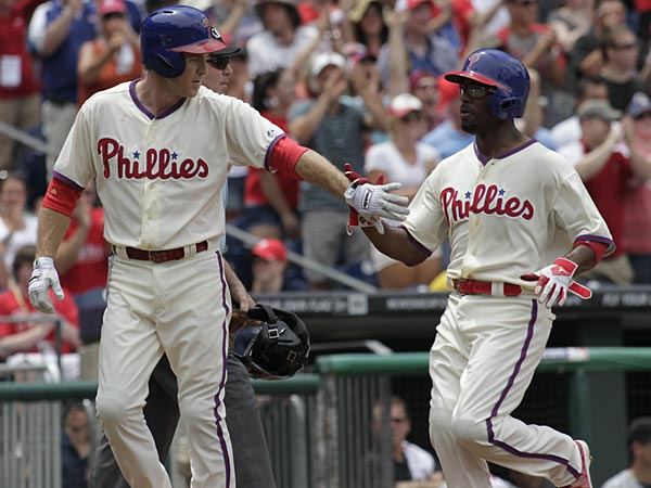 Chase Utley, left, and Jimmy Rollins celebrate after they scored against the White Sox in the first inning on Sunday. (H. Rumph Jr/AP)