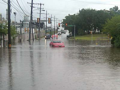 A car tries to navigate flooding at the intersection of Post and Price in Trainer, Delaware County. (Mari Schaefer / Staff)