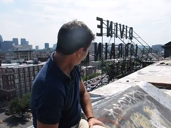 Developer Eric Blumenfeld sits on top of the Divine Lorraine Hotel in Philadelphia. (via YouTube)