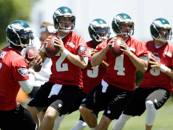 Eagles quarterbacks, from left, Michael Vick, Matt Barkley, Dennis Dixon, G.J. Kinne, and Nick Foles drop back to pass during NFL football practice at the team´s training facility, Tuesday, June 4, 2013, in Philadelphia. (Matt Rourke/AP file)