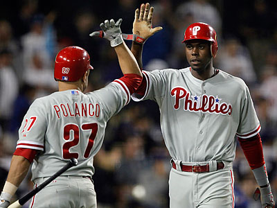 Placido Polanco congratulates John Mayberry Jr for scoring during the eighth inning. (Alex Gallardo/AP)