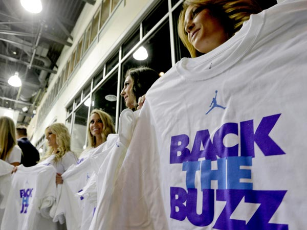 "Charlotte Bobcats dance team members hold ""Back The Buzz"" t-shirts after a news conference in Charlotte, N.C., Tuesday, May 21, 2013. The Bobcats announced they will be changing their name to the Hornets. (Chuck Burton/AP)"