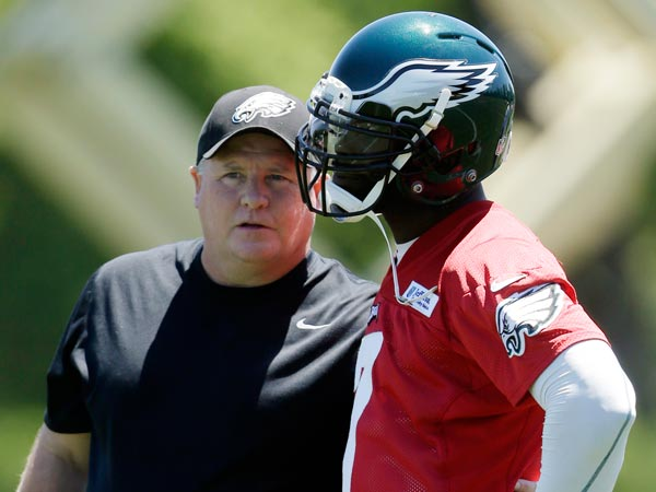 Chip Kelly (left) talks with quarterback Michael Vick during NFL football practice at the team´s training facility, Tuesday, June 4, 2013, in Philadelphia. (Matt Rourke/AP file)