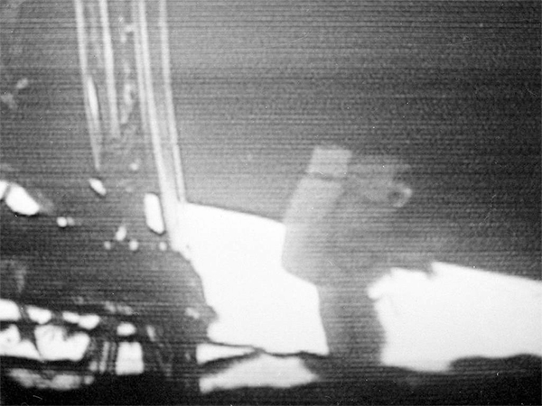 Neil Armstrong walking slowly away from the lunar module to explore the surface of the moon in this photo made from a TV monitor.