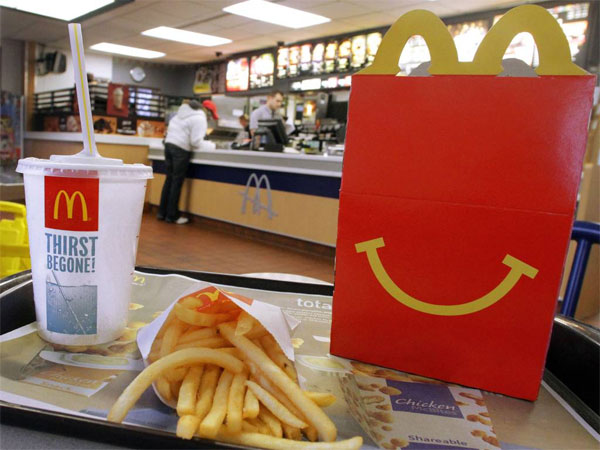In this Jan. 20, 2012 photo, the McDonald´s logo and a Happy Meal box with french fries and a drink are posed at McDonald´s. (AP Photo/Seth Perlman)
