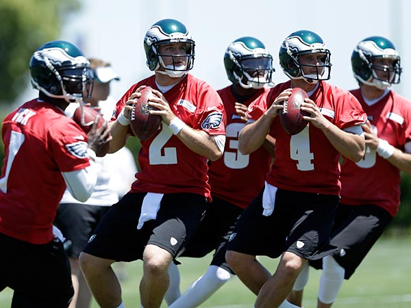 Philadelphia Eagles quarterbacks, from left, Michael Vick, Matt Barkley, Dennis Dixon, G.J. Kinne, and Nick Foles drop back to pass during NFL football practice at the team´s training facility, Tuesday, June 4, 2013, in Philadelphia. (AP Photo/Matt Rourke)