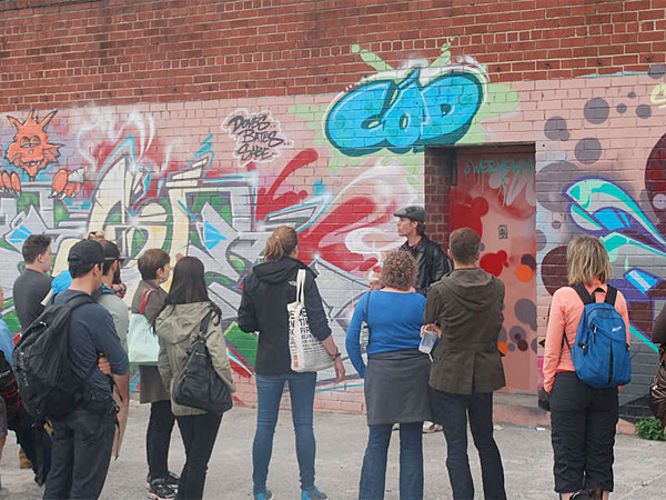 A tour guide explains the details of this graffiti, by an artist called Cod and his crew, who work out the details of the piece beforehand, then execute the work quickly at night.