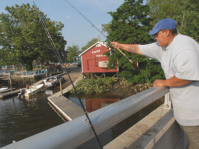 On a bridge overlooking Curtin´s Marina in Burlington City, Joel Rosario of Bensalem, Pa., tries to beat the heat and catch fish. (April Saul / Staff Photographer)