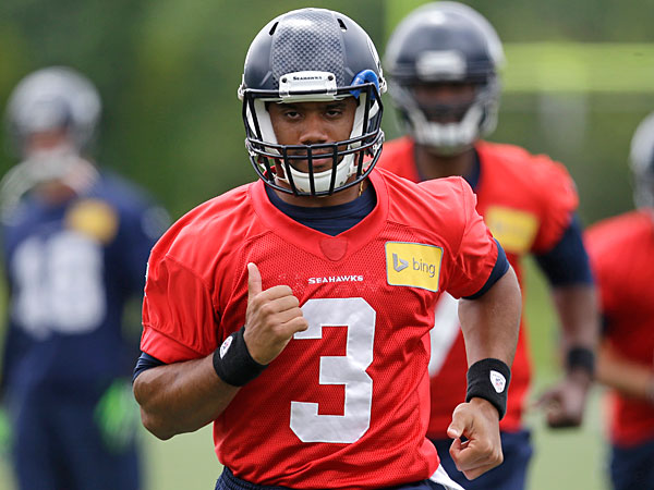 Seahawks quarterback Russell Wilson leads teammate through a drill at a football minicamp practice Tuesday, June 17, 2014, in Renton, Wash. (Elaine Thompson/AP)