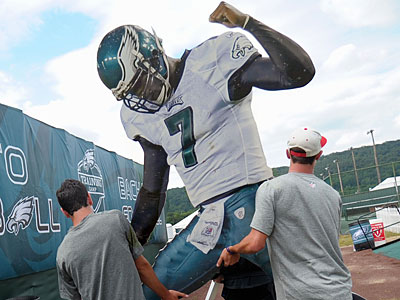 Eagles marketing interns carry a large cutout of quarterback Michael Vick to a spot at training camp. (AP Photo/The Express-Times, Matt Smith)