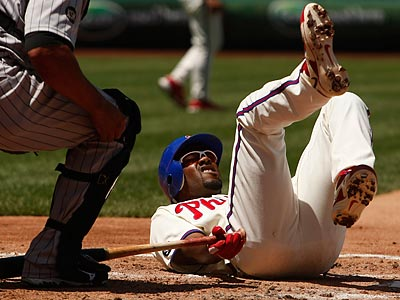 Jimmy Rollins falls to the ground after fouling a pitch off his left foot. (Ron Cortes / Staff Photographer)
