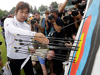 South Korea´s Im Dong-hyun collects his arrows after setting a world record in the round with a 699 score. (AP Photo/Marcio Jose Sanchez)