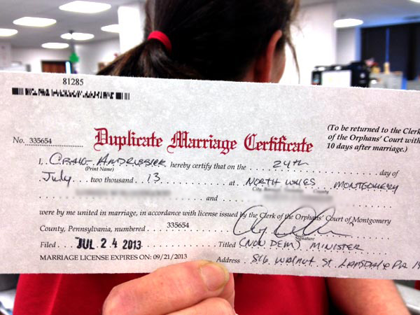 A staffer in the Montgomery County Register of Wills department, who did not want to be identified, holds up the first marriage license for a gay couple. (JESSICA PARKS / Staff)