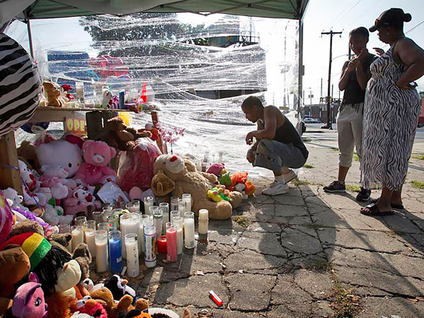 Mourners visit the shrine at Allegheny and Germantown Avenues where three young children were killed.