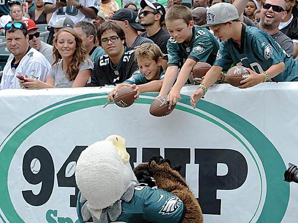 Young Eagles fans ask Eagles mascot Swoop to sign their footballs. (Clem Murray/Staff Photographer)