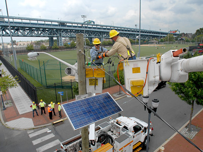 """Linemen Terry Lane (left) and Mike Gregory install a solar panel at Linden Street and Delaware Avenue in Camden as part of Public Service Electric and Gas's """"Solar 4 All"""" project. (April Saul / Staff Photographer)<br />"""