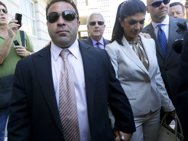 "Giuseppe ""Joe"" Giudice, 43, left, and his wife, Teresa Giudice, 41, of Montville Township, N.J., walk out of Martin Luther King, Jr. Courthouse after a court appearance, Tuesday, July 30, 2013, in Newark, N.J. (AP Photo/Julio Cortez)"