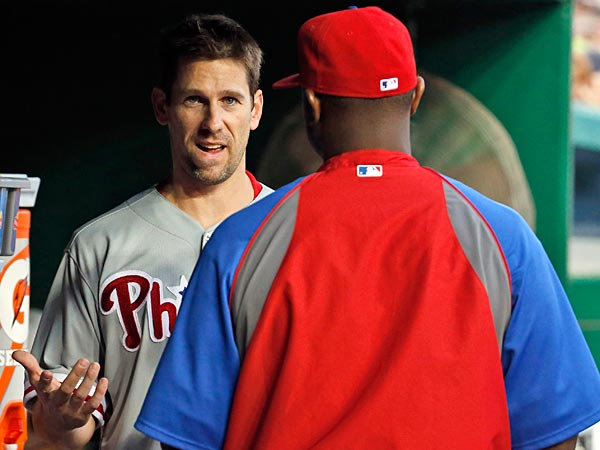 Phillies starting pitcher Cliff Lee, left, talks with Ryan Howard during the fourth inning of a baseball game against the Washington Nationals at Nationals Park Thursday, July 31, 2014, in Washington. Lee left the game during the third inning. The Phillies announced that Lee had a recurrence of the left flexor pronator strain that sidelined him in May. (Alex Brandon/AP)