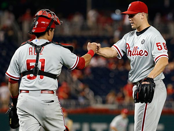 Phillies catcher Carlos Ruiz (51) celebrates with relief pitcher Jonathan Papelbon (58) after a baseball game against the Washington Nationals at Nationals Park Thursday, July 31, 2014, in Washington. The Phillies won 10-4. (Alex Brandon/AP)