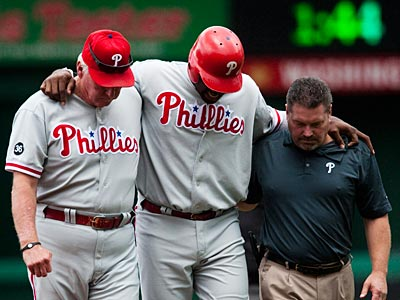 Ryan Howard is helped off the field during the first inning of today´s game. (Drew Angerer / AP Photo)