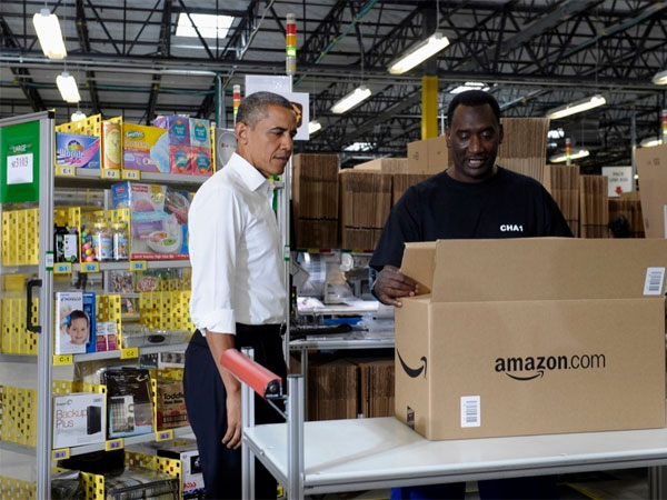 President Barack Obama talks with Eric Phillips as he tours the Amazon fulfillment center in Chattanooga, Tenn., Tuesday, July 30, 2013. Obama came to Chattanooga to give the first in a series of policy speeches on his proposals for private sector job growth and to strengthen the manufacturing sector. (AP Photo/Susan Walsh)