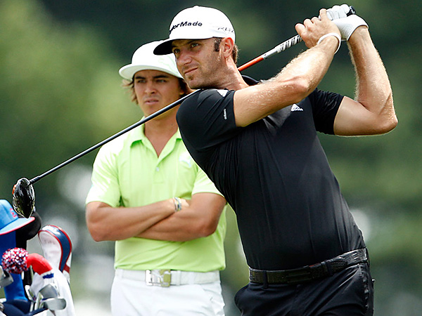 Dustin Johnson hits as Rickie Fowler watches.  (Yong Kim/Staff file photo)
