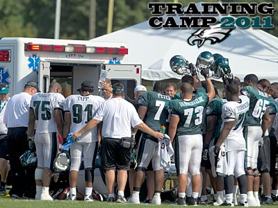 Eagles players huddle as Mike Patterson is loaded into an ambulance Wednesday. (Ed Hille/Staff Photographer)