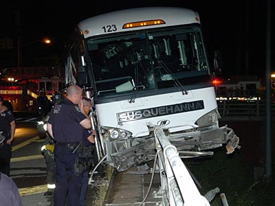 A bus carrying the Williamsport Crosscutters teeters on a guardrail after it crashed on the Staten Island Expressway. (Michael Oates/NY Post)
