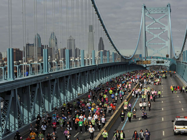 Runners and walkers cross the Ben Franklin Bridge during a benefit event. Officials say that up to 100,000 pedestrians will cross the bridge each day of Pope Francis' visit — and that each will be screened. (APRIL SAUL / File Photograph)