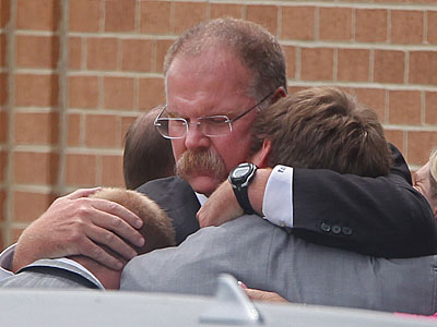 Andy Reid embraces his sons Britt, left, and Spencer following Garrett Reid´s funeral service. (Michael Bryant/Staff Photographer)