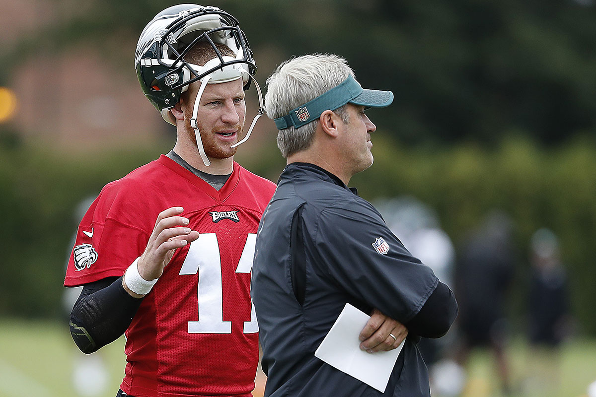 Carson Wentz (left) talks with head coach Doug Pederson during training camp.